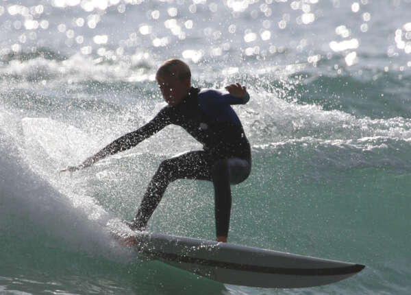 An improver surfers practicing the technique learnt on a surf lesson at Praa Sands, Cornwall