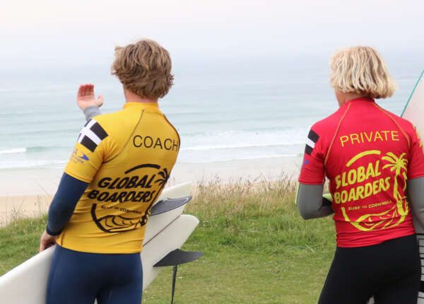 Global Boarders Surf Coach working 1-on-1 with a customer overlooking Gwithian beach before their improver surf lesson.