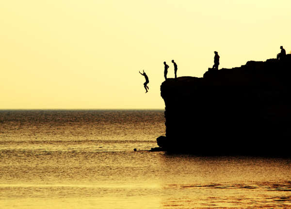 Jumping from a cliff into the sea during a coasteering lessons in Cornwall